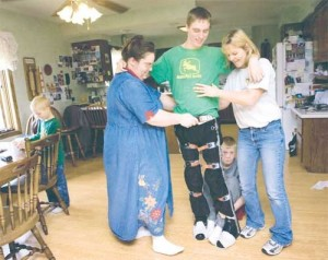 David Sparby moves his legs as his mother Tami (right) and Karen Olufson, a personal care attendant, help support his upper body. His brother Briley keeps his legs separated and David's younger brother Levi (far left) records David's progress.