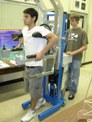 NIST research assistants demonstrate one function of the prototype robotic HLPR chair, facilitating leg exercise. (Image courtesy of National Institute of Standards and Technology)