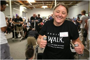 Darla Greven of Oregon, who was injured in a car accident with a drunk driver, smiles Saturday as she crosses the finish line after making her first walk since the accident during the Steps of Recovery fundraiser at Project Walk, a spinal cord injury recovery center in Carlsbad.