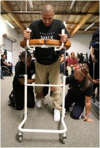 Jose Espinoza of Gardena, who was injured in a drive-by shooting, walks for the first time since the shooting with the help of specialists Tim Stevens and Kimberly Davis during the Steps to Recovery fundraiser Saturday at Project Walk, a spinal cord injury recovery center in Carlsbad. HAYNE PALMOUR IV Staff Photographer