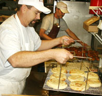 Eric fries the cinnamon rolls while Kirk glazes the shop's specialty, huge 5-by-5-inch apple fritters.
