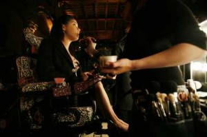 Michele Boardman, of Marleysville, Pa., in a wheelchair dressed up by fashion designer Kimora Lee Simmons, has her makeup applied before the gala.