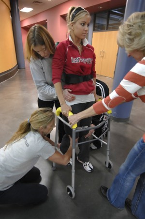 """Therapists help guide Kadi DeHaan's legs and feet as she walks through the hallway at MVP gym in Rockford. The movements must be """"ingrained neurologically"""" before they will become automatic, said therapist Sandy Burns."""
