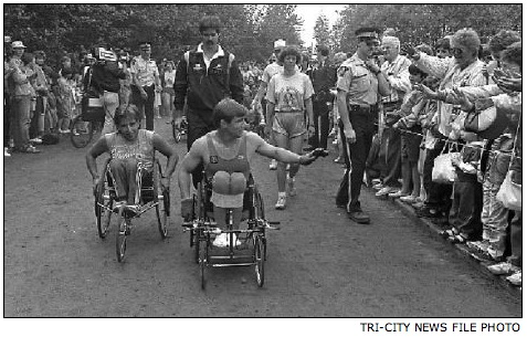 Rick Hansen wheels around the oval across from Centennial secondary school in Coquitlam in 1987, on the final day of the Man in Motion tour. Thousands packed the grounds to get a glimpse.