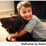Zachery Snider hugs his dog, Snoopy, who suffered a spinal cord injury in April.