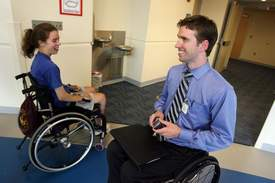 Brian Sheridan, 31, of Royal Oak, talks to Molly Fausone, 17, of Wilmette, Ill., who is recovering from a spinal cord injury at the Rehabilitation Institute of Michigan in Detroit.