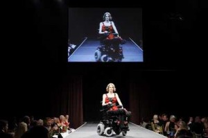 """Jenny Smith of Louisville, Ky., appears on a screen above as she makes her way down the runway on a wheelchair decorated by fashion designer Zang Toi during the """"Rolling with Style"""" gala, a fashion fundraising event Tuesday benefiting women's health and spinal cord research in New York. The wheelchairs used in the event were manufactured in Fresno."""
