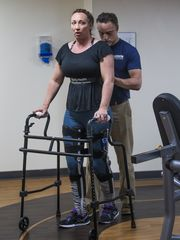 Amy Van Dyken-Rouen takes a lap, using a brace and a walker, with help from physical therapist Al Biemond at the Barrow Neurological Institute in Phoenix, (Photo: Tom Tingle/The Republic, azcentral.com)