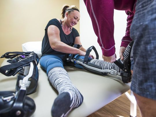 Amy Van Dyken Rouen has progressed from walking in an exoskeleton to walking with a brace that requires her to use more of her core stability and leg control. She gets help with her braces from husband, Tom Rouen, right, at the Barrow Neurological Institute in Phoenix. (Photo: Tom Tingle/The Republic, azcentral.com)