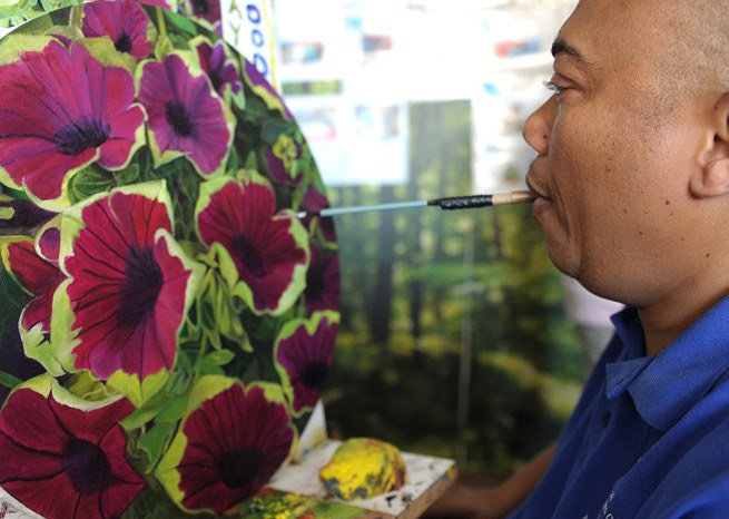 Martin Sodoms uses his mouth to paint during the Arts fun day at Sibongile Care Centre in Khayelitsha. Picture: Cindy Waxa/Cape Argus