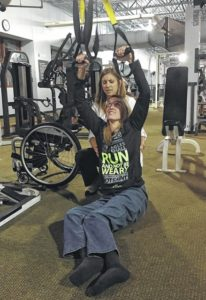 Melonie McLaurin | Daily Journal Katie Sewell, a physical therapist, assists Kandace Frye with a form of modified pull-ups using equipment at FirstHealth Fitness Center in Richmond County. Frye sustained a T4 complete spinal cord injury in 2014.