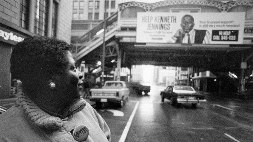 Lemmie Jennings, mother of paralyzed Simeon High School football player Kenneth Jennings, looks at a billboard on a CTA L station at Randolph and Wells streets seeking financial help for the family in January 1989.(John Dziekan / Chicago Tribune)