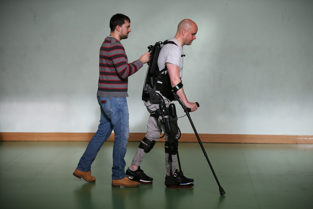 ALL IMAGES COPYRIGHT MARK POLLOCK TRUST. Mark Pollock is helped by his assistant as he walks using the Ekso Bionics robotic exoskeleton at Trinity College in Dublin 7th November 2015. Photographed by Peter Macdiarmid for the Mark Pollock Trust.
