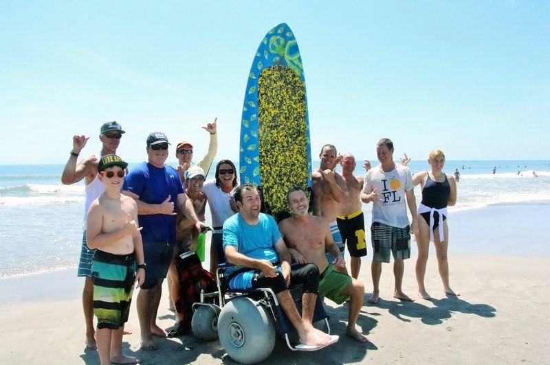 "It took a team of delighted friends and family to help Florida engineer Matt Bellina (center) get back on his surfboard this summer after his severe spinal injury. The result? ""I feel like I'm home,"" Bellina said. Courtesy of Diane Wehrell-Grabowski"