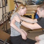 Smiling through the pain, Teresa Hukari works to develop core body strength with a Physical Therapist at Project Walk.