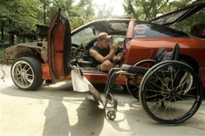 Chris Hrabik, 21, works on his customized 1993 Nissan 240SX as his wheelchair sits near by Thursday, Aug. 2, 2007, in Oak Ridge, Mo. More than a year after his return from China where he received stem cell therapy, Hrabik says he has nearly complete use of his left hand and improvement in the right, reversing paralysis caused by a car accident near his 18th birthday.