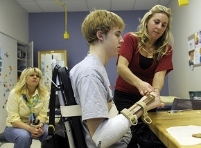 Derek Zike, 17, who broke his neck during a hockey game in Ann Arbor, works with occupational therapist Jamie Leigh Baltzell. (Clarence Tabb Jr./The Detroit News)