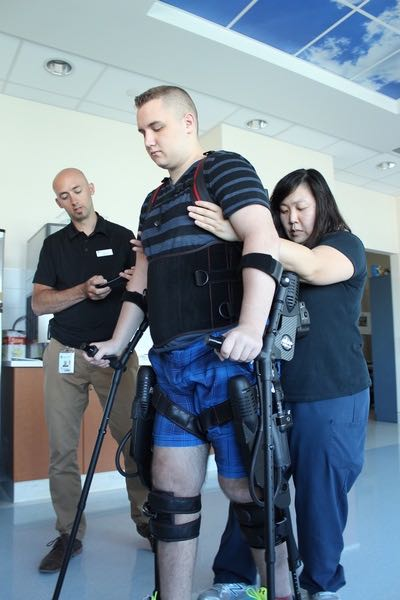 Physical therapist Kyle McIntosh, left, and Olivia Dong, right, a clinical leader in physiotherapy, help spinal injury patient Alex in a rehabilitation session.