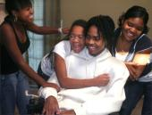 Arquevious 'Q' Crane laughs with his three sisters — Tiffany Crane(from left), 12, Zakiyyah Salaam, 11, and Khadijah Salaam, 14 — while playing a video game. He suffered a spinal injury during a football game Sept. 20.