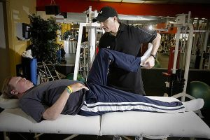 Clinical physiologist Taylor Kevin Isaacs stretches Tom Bolewski during their therapy session. Bolewski will be standing on his own at monday's Los Angeles Marathon. (David Crane/Staff Photographer)