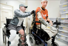 Air Force Senior Airman Brian G. Kolfage, right, a triple amputee, was wounded in a mortar attack in Iraq in 2004. He receives help from a friend, Mike Sanchez, on Thursday, April 14, 2005 at Walter Reed Army Medical Center in Washington, D.C. (mvw) 2005